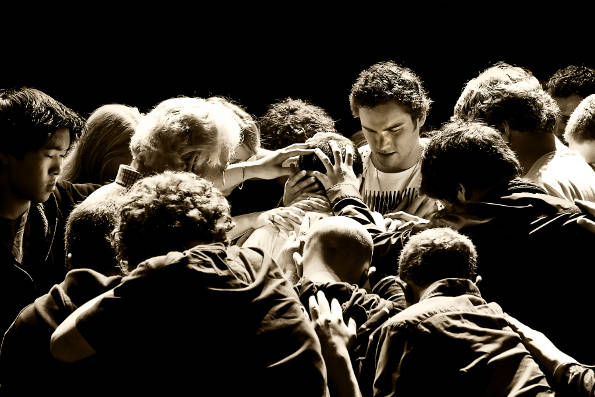Image of a Group of People Laying Hands on Someone to Pray
