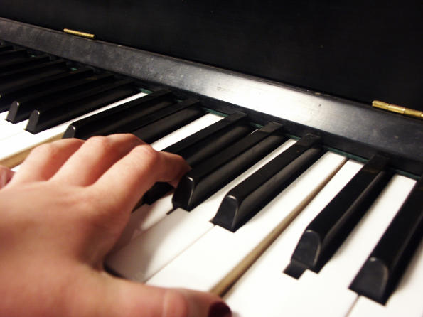 Hand playing piano keys.