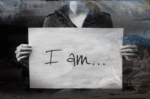 """Image of a faceless person holding a sign that says, """"I am..."""""""