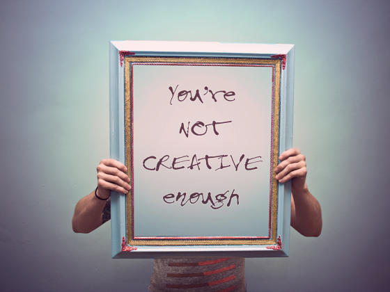 "Image of a man holding a canvas in front of his face with words ""Not creative enough"""
